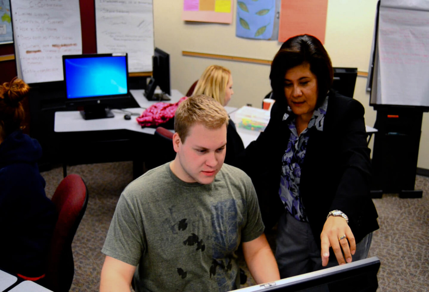 Instructor advising student over computer
