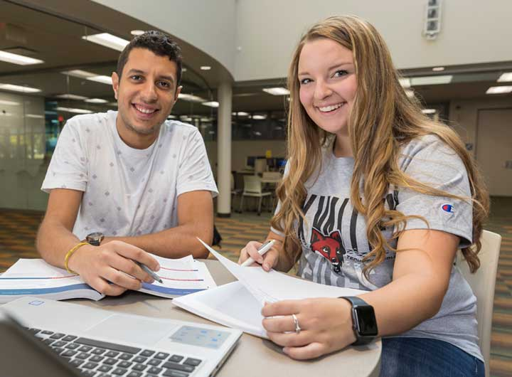 Two students studying together and smiling