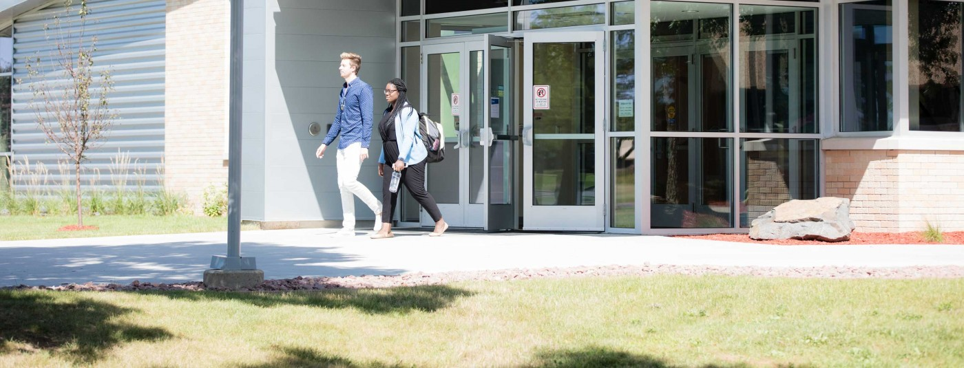 Two students walking outside campus building