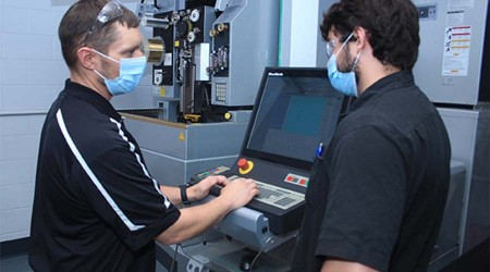 Two people with face masks working with machine