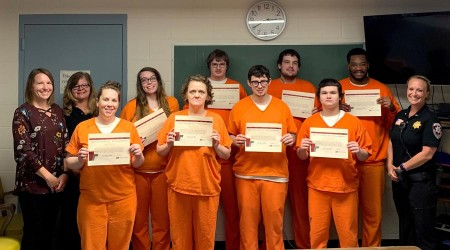 Inmates smiling with achievement awards