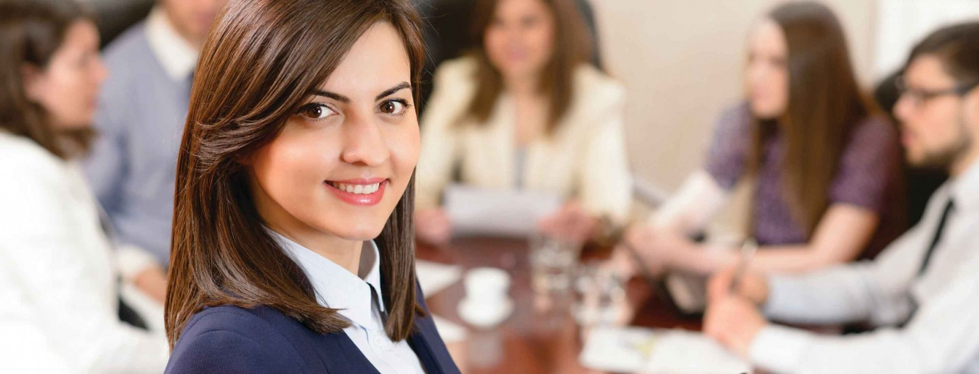 Professionally dressed person smiling at conference meeting